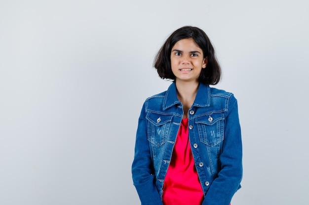 Jong meisje staat rechtop en poseert voor de camera in een rood t-shirt en spijkerjasje en ziet er gelukkig uit.