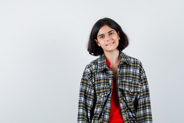 Jong meisje staat rechtop en poseert voor de camera in geruit overhemd en rood t-shirt en ziet er gelukkig uit. vooraanzicht.