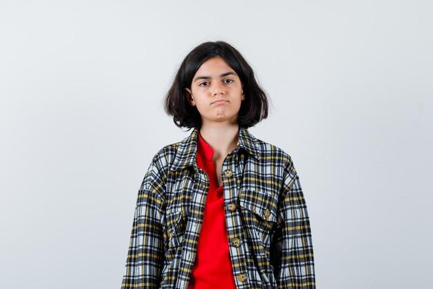 Jong meisje staat rechtop en poseert voor de camera in geruit overhemd en rood t-shirt en ziet er serieus uit. vooraanzicht.