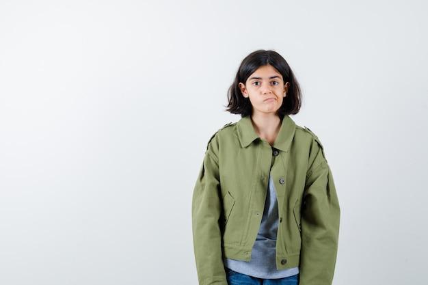 Jong meisje staat rechtop, grimast en poseert in een grijze trui, kaki jas, spijkerbroek en ziet er schattig uit. vooraanzicht.