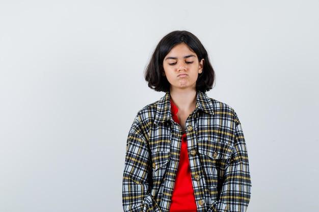 Jong meisje staat rechtop, kijkt naar beneden en poseert voor de camera in geruit overhemd en rood t-shirt en ziet er serieus uit. vooraanzicht.