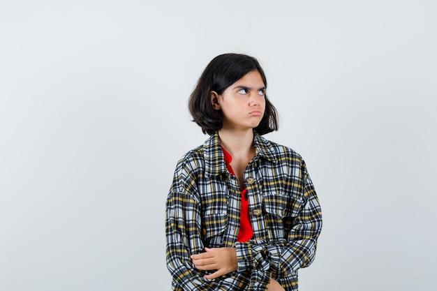 Jong meisje staat rechtop, kijkt weg en poseert voor de camera in geruit overhemd en rood t-shirt en kijkt geïrriteerd. vooraanzicht.