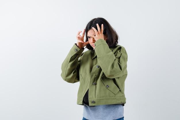 Jong meisje steekt handen op een boze manier op in grijze trui, kaki jas, spijkerbroek en kijkt geïrriteerd. vooraanzicht.