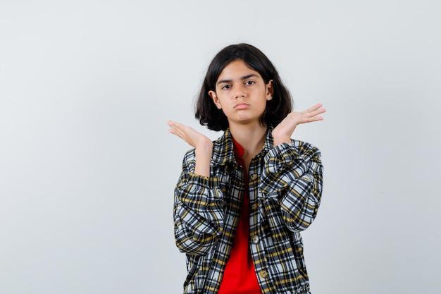 Jong meisje steekt handen op in de buurt van gezicht in geruit overhemd en rood t-shirt en ziet er serieus uit. vooraanzicht.