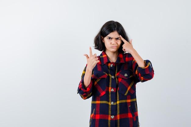 Jong meisje steekt wijsvinger op in eureka-gebaar terwijl ze aan iets in geruit overhemd denkt en peinzend kijkt. vooraanzicht.
