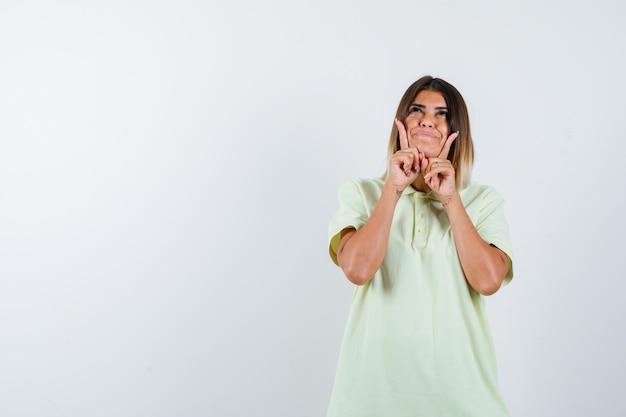 Jong meisje steunt kin bij de hand, wijst naar boven, kijkt omhoog in t-shirt en kijkt vrolijk, vooraanzicht.