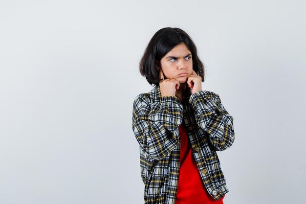 Jong meisje stopt oren met wijsvingers in geruit overhemd en rood t-shirt en kijkt geïrriteerd. vooraanzicht.