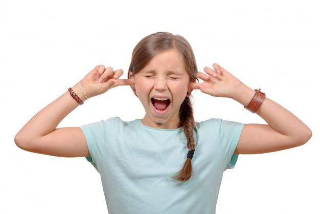Jong meisje stopt zijn oren met zijn handen en sluit zijn ogen