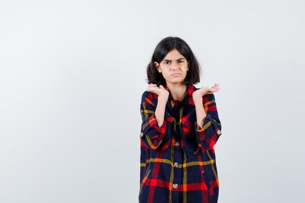 Jong meisje strekt haar handen op vragende manier uit in een geruit overhemd en kijkt verbaasd, vooraanzicht.