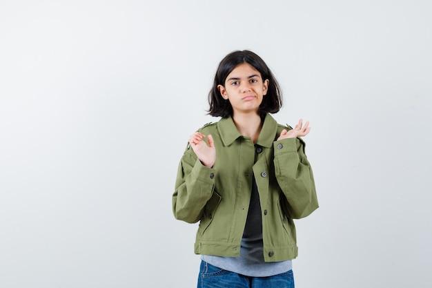 Jong meisje strekt haar handen op vragende manier uit in grijze trui, kaki jas, jeansbroek en kijkt verbijsterd, vooraanzicht.