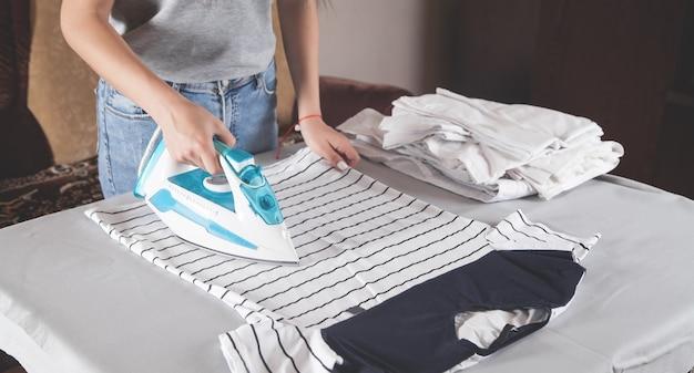 Jong meisje strijken t-shirt in huis.