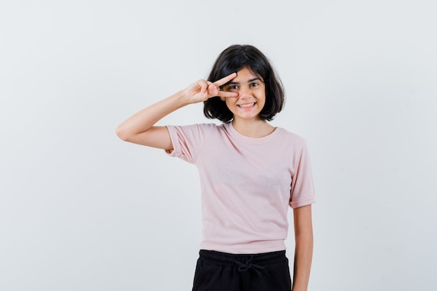 Jong meisje toont v-teken op oog in roze t-shirt en zwarte broek en ziet er schattig uit