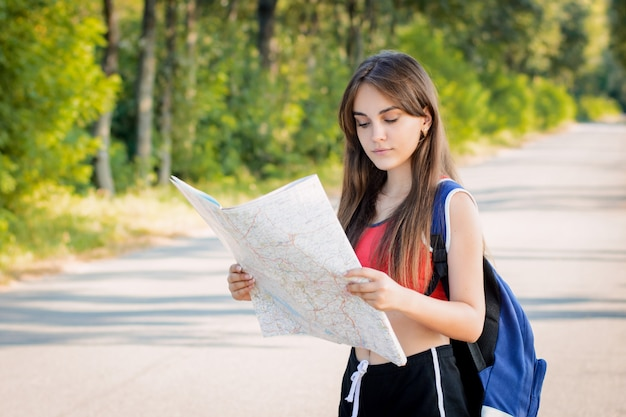 Jong meisje verdwaalde op het platteland terwijl ze alleen reisde en probeert een richting te vinden met een papieren kaart