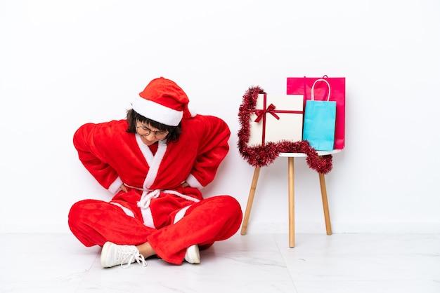 Jong meisje viert kerstmis zittend op de vloer geïsoleerd op een witte achtergrond die lijdt aan rugpijn omdat ze moeite heeft gedaan
