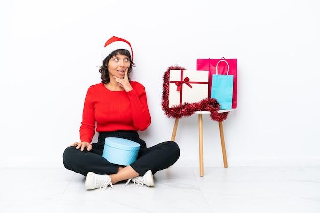 Jong meisje viert kerstmis zittend op de vloer geïsoleerd op een witte achtergrond en denkt aan een idee terwijl ze omhoog kijkt