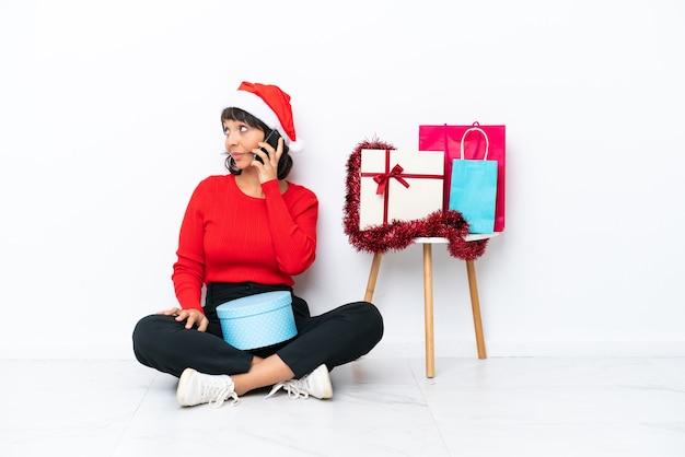 Jong meisje viert kerstmis zittend op de vloer geïsoleerd op een witte achtergrond en houdt een gesprek met de mobiele telefoon met iemand