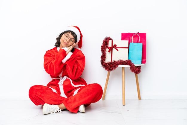 Jong meisje viert kerstmis zittend op de vloer geïsoleerd op een witte achtergrond en maakt een slaapgebaar in een schattige uitdrukking