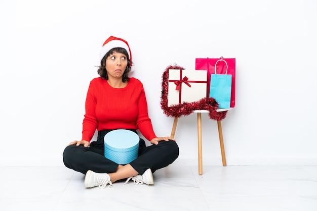 Jong meisje viert kerstmis zittend op de vloer geïsoleerd op een witte achtergrond en maakt twijfels gebaar terwijl ze de schouders optilt