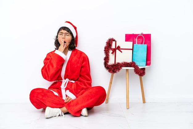Jong meisje viert kerstmis zittend op de vloer geïsoleerd op een witte achtergrond, geeuwen en wijd open mond met de hand bedekken