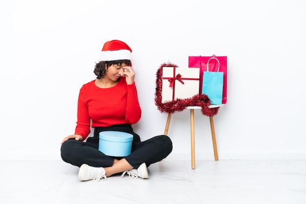 Jong meisje viert kerstmis zittend op de vloer geïsoleerd op een witte achtergrond lachen