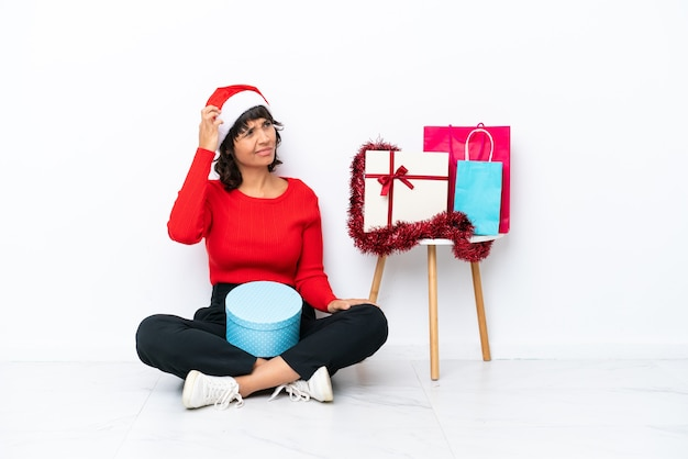 Jong meisje viert kerstmis zittend op de vloer geïsoleerd op een witte achtergrond met twijfels en met een verwarde gezichtsuitdrukking