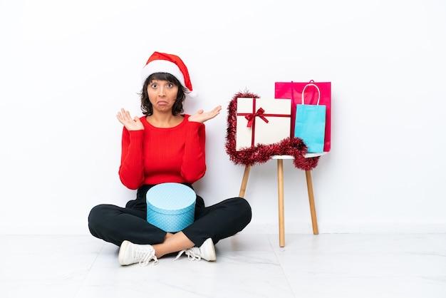 Jong meisje viert kerstmis zittend op de vloer geïsoleerd op een witte achtergrond met twijfels tijdens het opsteken van de handen