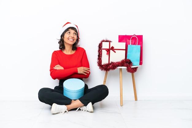 Jong meisje viert kerstmis zittend op de vloer geïsoleerd op een witte achtergrond terwijl ze glimlacht