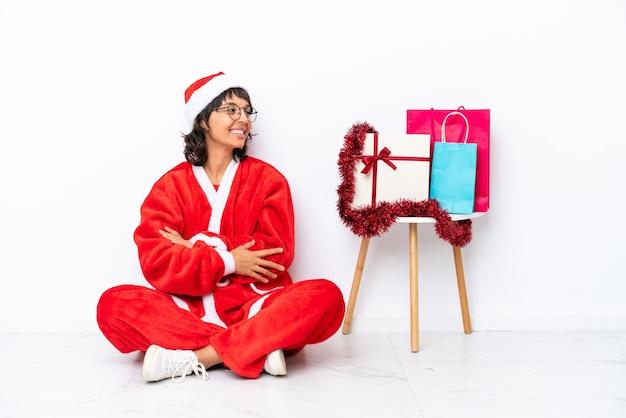 Jong meisje viert kerstmis zittend op de vloer geïsoleerd op een witte bakcground in laterale positie