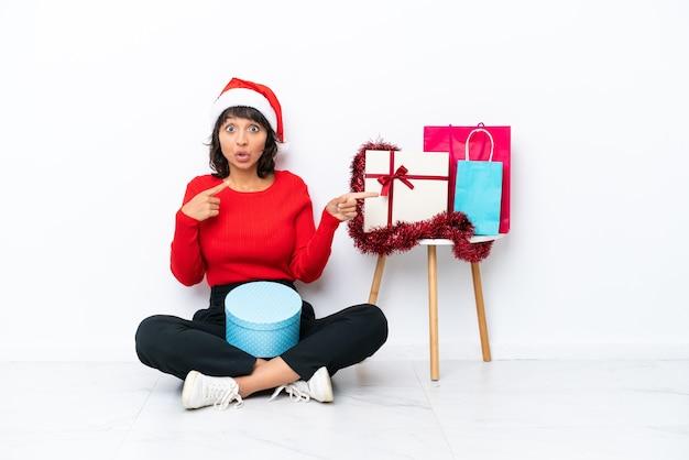 Jong meisje viert kerstmis zittend op de vloer geïsoleerd op een witte bakcground verrast en wijzende kant