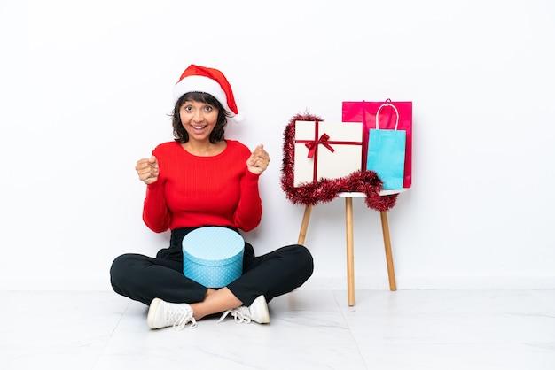 Jong meisje viert kerstmis zittend op de vloer geïsoleerd op een witte bakcground viert een overwinning in winnaar positie