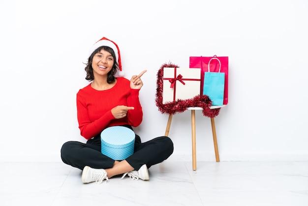 Jong meisje viert kerstmis zittend op de vloer geïsoleerd op een witte bakcground wijzende vinger naar de zijkant en presenteren van een product