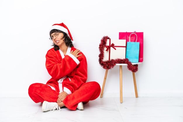 Jong meisje viert kerstmis zittend op de vloer geïsoleerd op een witte ondergrond die lijdt aan pijn in de schouder omdat ze moeite heeft gedaan