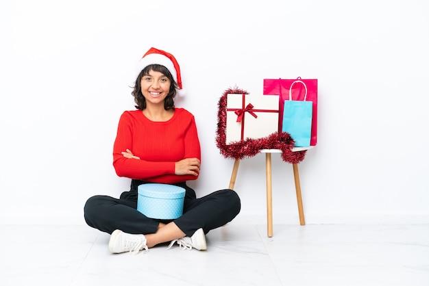 Jong meisje viert kerstmis zittend op de vloer geïsoleerd op een witte ondergrond, waarbij de armen in frontale positie worden gekruist