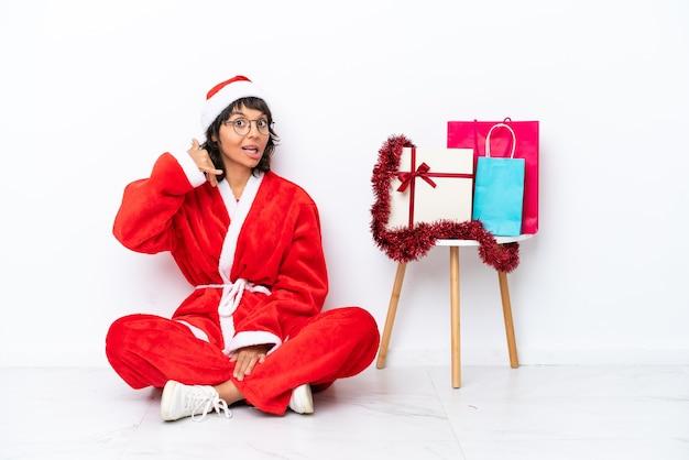 Jong meisje viert kerstmis zittend op de vloer geïsoleerd op witte bakcground telefoon gebaar maken. bel me terug teken