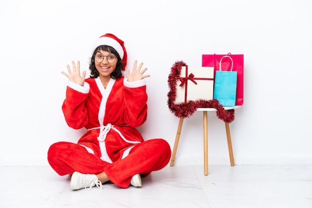 Jong meisje viert kerstmis zittend op de vloer geïsoleerd op witte bakcground tien tellen met vingers