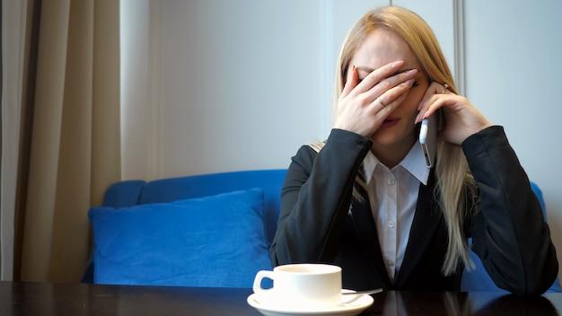 Jong meisje voelt zich verdrietig en huilt terwijl ze met iemand op mobiel praat, close-up