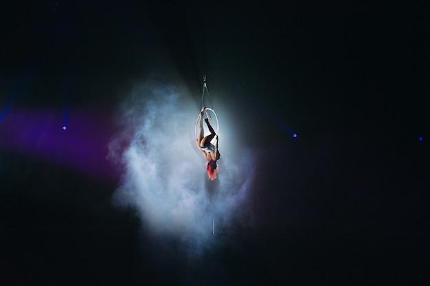 Jong meisje voert de acrobatische elementen in de luchtring uit
