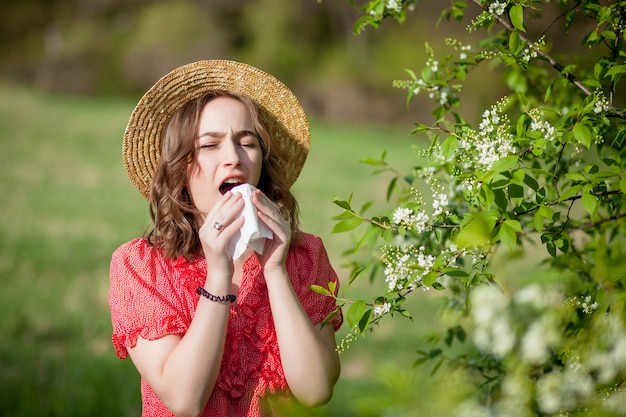Jong meisje waait neus en niezen in weefsel voor bloeiende boom