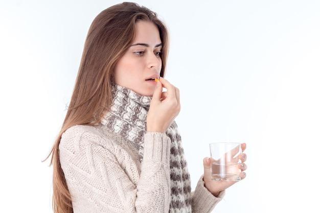Jong meisje werd ziek en dronk kuren met in haar hand een glas water close-up
