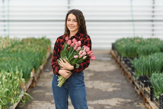 Jong meisje, werknemer met bloemen in kas