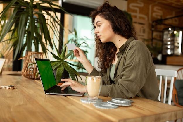 Jong meisje werkt in een coffeeshop met een laptopvrouwelijke freelancer met een creditcard