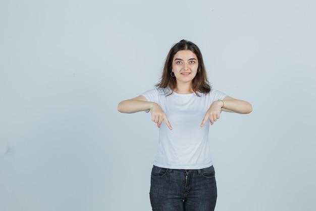 Jong meisje wijst naar beneden in t-shirt, spijkerbroek en kijkt zelfverzekerd, vooraanzicht.