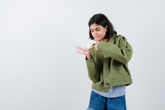 Jong meisje wijst naar de hand in grijze trui, kaki jas, jeansbroek en kijkt gefocust, vooraanzicht.