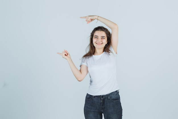 Jong meisje wijst naar de zijkant in t-shirt, spijkerbroek en kijkt gelukkig. vooraanzicht.