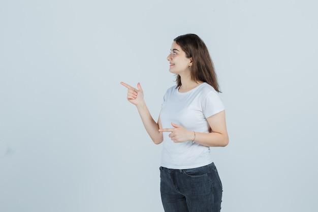 Jong meisje wijst naar de zijkant in t-shirt, spijkerbroek en op zoek verstandig, vooraanzicht.