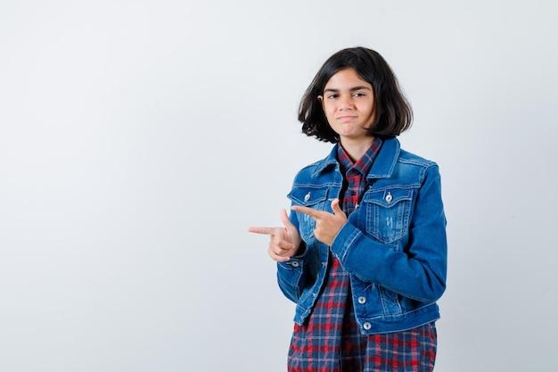 Jong meisje wijst naar links met wijsvingers in geruit overhemd en spijkerjasje en ziet er schattig uit, vooraanzicht.