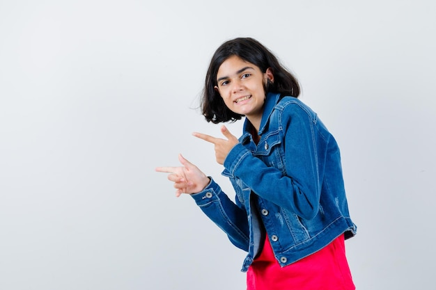 Jong meisje wijst naar links met wijsvingers in rood t-shirt en spijkerjasje en ziet er gelukkig uit. vooraanzicht.