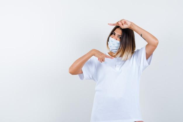 Jong meisje wijst naar rechts en links met wijsvingers in wit t-shirt en masker en kijkt zelfverzekerd, vooraanzicht.