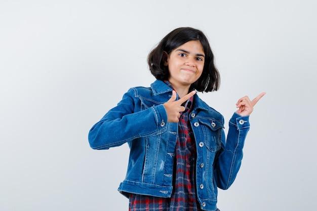 Jong meisje wijst naar rechts met wijsvingers in geruit overhemd en spijkerjasje en ziet er schattig uit