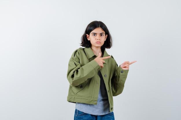Jong meisje wijst naar rechts met wijsvingers in grijze trui, kaki jas, jeansbroek en ziet er serieus uit, vooraanzicht.
